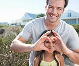 Father forming heart_shape in front of daughter's face