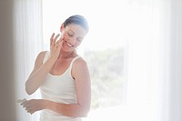 Smiling woman applying moisturizer to face (thumbnail)
