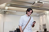 Smiling businessman text messaging on cell phone in office