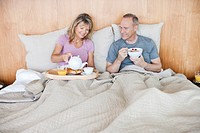 Senior couple eating breakfast in bed