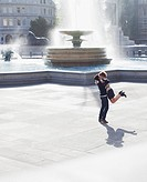 Man lifting woman in front of urban fountain