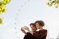 Couple taking self_portrait with digital camera below ferris wheel