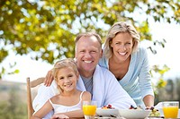 Portrait of smiling parents and daughter enjoying breakfast at table in garden