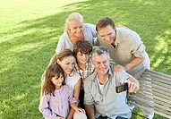 Smiling multi_generation family taking self_portrait with digital camera on park bench