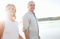 Portrait of smiling senior couple walking on beach