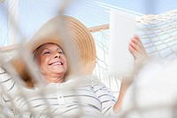 Smiling woman laying in hammock and using digital tablet