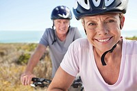 Close up portrait of smiling senior couple riding bicycles