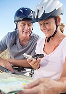 Senior couple in bicycle helmets looking at compass and map