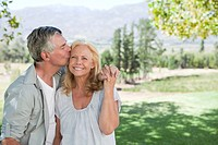 Senior man kissing woman in sunny rural field