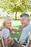 Portrait of senior couple drinking white wine in garden