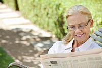 Smiling senior woman reading newspaper on park bench