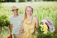 Smiling couple with flowers in rural field