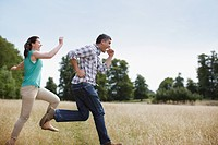 Playful couple running in rural field