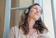 Calm woman listening to music on headphones in window (thumbnail)
