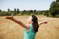 Woman with arms outstretched in sunny rural field