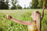 Smiling woman with arms outstretched in rural field