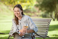 Portrait of smiling woman drinking white wine and reading magazine on park bench