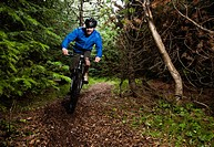 Man mountain biking on dirt path