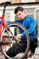 Mid adult man adjusting bicycle wheel