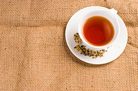Red tea in ceramic cup with burlap background