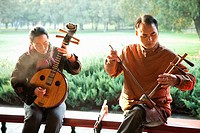 China,Beijing,Temple of Heaven Park, Man and Woman Playing Traditional Chinese Stringed Instruments