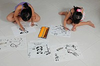 Young girls drawing pictures with Chinese brush and ink