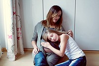 Daughter listening to pregnant mother´s abdomen, mother caressing daughter´s hair, portrait