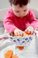 Infant playing with bowl of carrots
