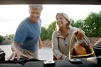Senior couple loading bags into car