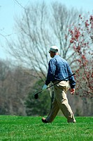 Male golfer walking on a golf course