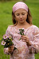 YOUNG TEN_YEAR_OLD GIRL PICKING FLOWERS IN THE COUNTRYSIDE