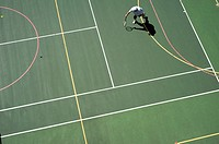 man playing tennis on tennis and basketball court