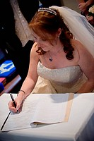 beautiful red hair bride signing the wedding register with a black pen