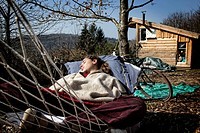 LORELEI TAKING A NAP IN A HAMMOCK, SHE LEFT EVERYTHING BEHIND TO COME BUILD AND LIVE IN HER WOOD CABIN IN THE CREUSE, FRANCE