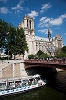 Tourist boat passing under Pont au Double beside Notre Dame Cathedral in Paris, France