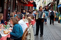 Accordion player entertains lunch time diners in Paris, France