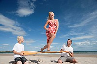 Woman jumping over paddle held by man and boy on sunny beach