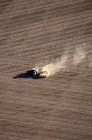 Aerial view of a tractor tilling brown fields to prepare for planting.