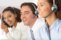 Smiling business people wearing headsets