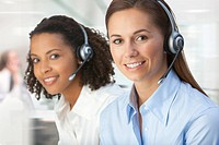 Close up portrait of smiling businesswomen wearing headsets