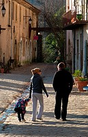 A family strolls through the historic village of Villeneuvette in the Midi region of France