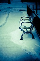 A wrought iron public bench covered with snow on a sidewalk that the snow has just been shoveled