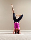37 year old brunette woman doing a yoga pose in a home interior setting