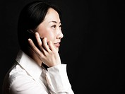 Young Asian Woman On Phone On Black Background.
