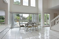 Two story eating area in luxury home with picture windows