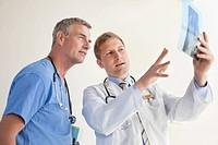Doctor explaining X_ray to male nurse