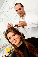 Hispanic woman having her hair cut in salon