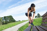 Chinese woman tying shoes before exercise