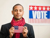 Hispanic man holding American flag with Vote sign in background