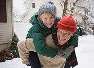 Caucasian father giving son piggy back ride through snow